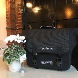 Brompton Ortlieb bag - Black Reflective next to some flowers
