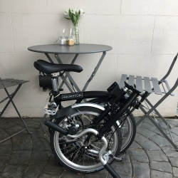Brompton 2017 M3L Black folded next to cafe table