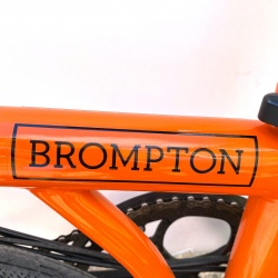 Brompton decal BLACK edition for GLOSS black edition frames shown on an orange Brompton